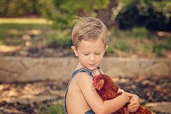 Little farm boy holding red chicken. Boy eating sandwich fishing bridge Royalty Free Stock Photography