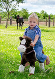 Little farm boy rides on toy rocking horse Stock Photography