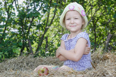 Little farm girl sitting on natural cereal straw bale at green tree leaves summer background. Little farm girl is sitting on natural cereal straw bale at green Royalty Free Stock Images