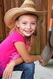 Little farm girl in a straw hat. A young cute little blond farm girl in pink shirt, and a straw hat. Shallow depth of field Royalty Free Stock Photos