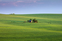 Little farm house with last sun lights in green field Stock Photo