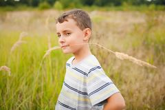 Little farmer. Cute kid chewing a straw of yellow grass, like the farmer he is Stock Images