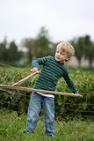 Little farmer. Toddler boy pretending to be a farmer with a scythe stock images