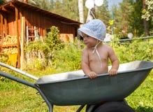 Little farmer and his wheelbarrow. Hot summer day Stock Photos