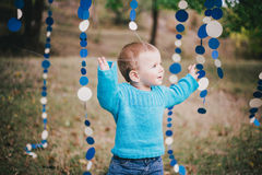 Little fashion boy in a forest wearing blue sweater and jeanse Stock Photo