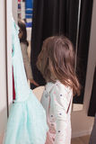 Little fashion conscious. Little pretty girl trying on dress in a fitting room Royalty Free Stock Photography