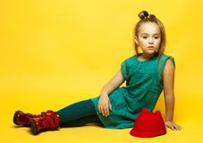 Little fashion girl with blond hair posing over yellow background royalty free stock photos