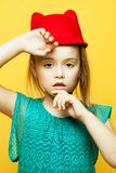 Little fashion girl with blond hair posing over yellow background stock photo
