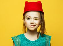Little fashion girl with blond hair posing over yellow background stock photography