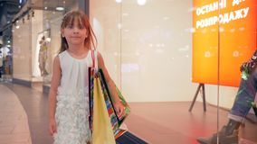 Little fashion-girl enjoys shopping during seasonal discounts of black Friday. In mall stock footage