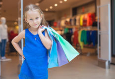 Little fashion girl with packages in a large Royalty Free Stock Images
