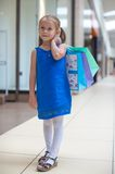 Little fashion girl with packages in large Royalty Free Stock Photography