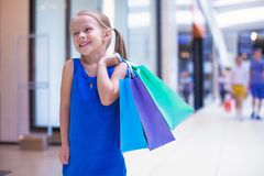Little fashion girl with packages in a large Royalty Free Stock Photos