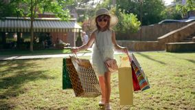 Little fashion-girl with shopping bags after visiting expensive boutiques walks on lawn and smiles. In sunlight stock video footage