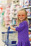 Little fashion girl with trolley in a large Royalty Free Stock Photography