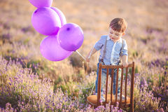 Little fashionable boy having fun in lavender summer field. Stock Photos