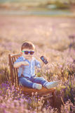 Little fashionable boy having fun in lavender summer field. Royalty Free Stock Image