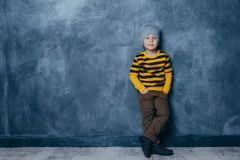 Little fashionable boy posing in front of a gray-blue concrete wall. Portrait of a smiling child dressed in a black and yellow stock photography