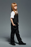 Little fashionable girl in black costume. Over grey background royalty free stock photos