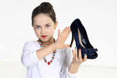 Little fashionista holding shoe. In studio Stock Photography