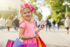 Little fashionista holding shopping bags. Fashionista holding shopping bags and smiling royalty free stock photo