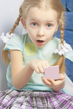 Little fasionable girl applying cosmetics. Cute little fasionable girl applying decorative cosmetics indoors and exclaiming Royalty Free Stock Photo