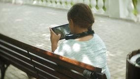 Little fat girl with a tablet PC and headphones sitting on a bench listening to music or watching a video in a summer. Park 4k stock footage