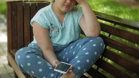 Little fat girl with a tablet PC and headphones sitting on a bench listening to music or watching a video in a summer. Park 4k stock video footage