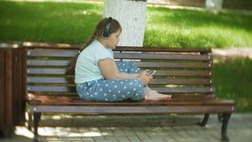 Little fat girl with a tablet PC and headphones sitting on a bench listening to music or watching a video in a summer. Park 4k stock video