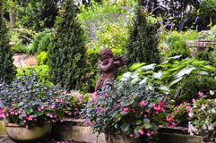 Little faun statue playing the flute in between flowers Stock Photo