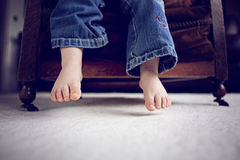 Little feet dangling over a chair. Little feet and legs dangling over a chair, which can almost reach the floor royalty free stock photos
