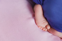 Little feet a newborn baby looking out from under blanket Royalty Free Stock Images