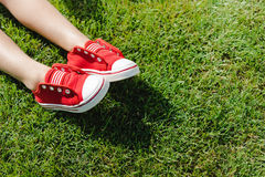 Little feet in red sneakers on green grass. Close-up partial view of little feet in red sneakers on green grass Royalty Free Stock Photos