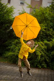 Little fellow flies over the yard with a yellow umbrella in hand Stock Images