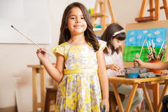Little female artist enjoying art class. Cute Hispanic little girl smiling in front of her classroom during art class stock image