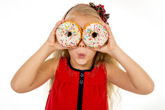 Little female child happy playing with two sugar donuts as her eyes Stock Photo