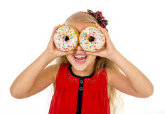 Little female child happy playing with two sugar donuts as her eyes Stock Photography