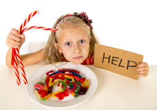 Little female child nutrition abuse of sweet and sugar in candy unhealthy food asking for help Royalty Free Stock Image