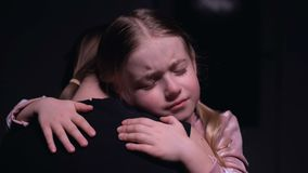 Little female kid hugging mother and crying, victims of domestic violence, fear. Stock footage stock footage