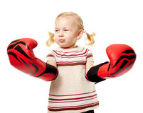 Little fighter. Little blond girl with huge boxing gloves, fighter spirit concept Royalty Free Stock Images