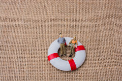 Little figurine men in a life preserver Stock Photo