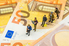 Little figurines standing in line on new 50 euro banknotes Stock Photos