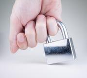 Little finger holding silver padlock. Little finger holding the used, scratchy, silver padlock  on white Stock Photo