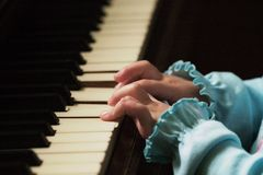 Little fingers playing the piano. Hands of a little girl playing the piano Stock Image