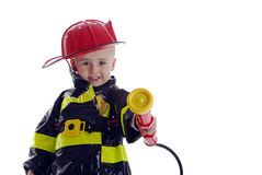 Little fire fighter toddler. Little boy fire fighter points water sprayer at camera Stock Images