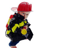 Little fire fighter toddler. Little boy fire fighter points water sprayer at camera Stock Image