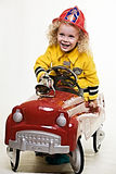 Little fireman. Portrait of an adorable little three year old boy wearing fireman costume sitting in a toy firetruck stock images