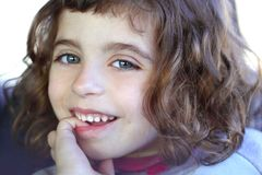 Little firl smiling shy biting finger blue eyes Stock Photography