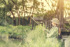 Little fisher girl holding a rod Royalty Free Stock Image