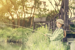 Little fisher girl holding a rod Royalty Free Stock Photos